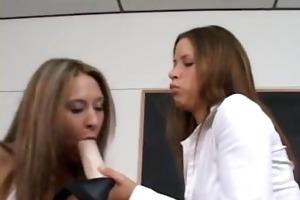 a lesbian sucks on a large dildo... really big!